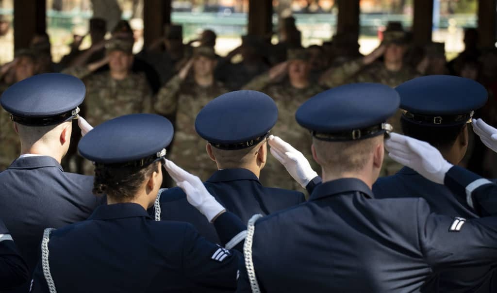 Pallbearers and Airmen in the audience salute during the Honor Guard graduation ceremony, March 6, at Eglin Air Force Base, Fla. Approximately 17 new Airmen graduated from the 120-plus-hour course. The graduation performance includes flag detail, rifle volley, pallbearers and bugler for friends, family and unit commanders. (U.S. Air Force photo by Samuel King Jr.)